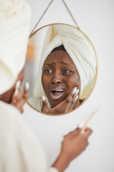 Vertical portrait of young african-american woman suffering from toothache and gum pain while brushing teeth in morning, copy space