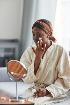 Vertical portrait of young african-american woman using face cream or moisturizer, skincare and beauty routine concept