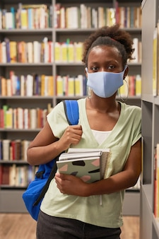 Vertical portrait of young africanamerican woman wearing mask while posing in school library and loo...