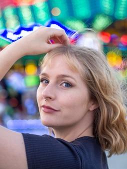 Ritratto verticale di una giovane donna bionda in un parco di divertimenti