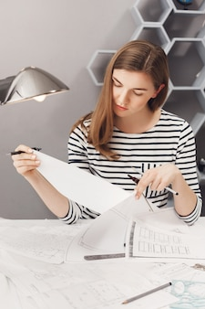 Vertical portrait of young good-looking female designer with brown hair in striped shirt, looking at papers with serious expression, working on new clothes designs for fashion show.