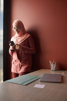 Vertical portrait of young muslim businesswoman using smartphone while standing against red wall in office, copy space