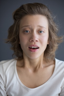 Vertical portrait of young startled lady sadly