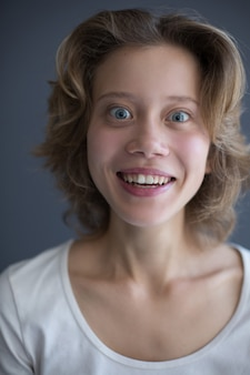 Vertical portrait of young surprised woman joyfully