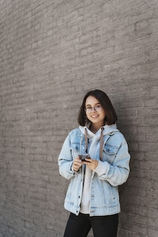 Vertical portrait of young teenage girl in glasses, denim spring outfit, leaning on a brick wall outdoors, holding mobile phone.