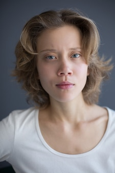 Vertical portrait of young thoughtful lady smirkingly