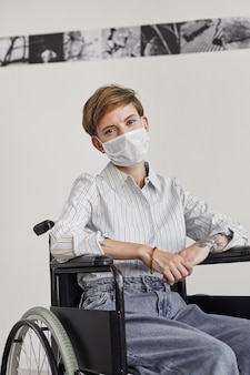 Vertical portrait of young woman using wheelchair and wearing mask while  against white wall in modern art gallery