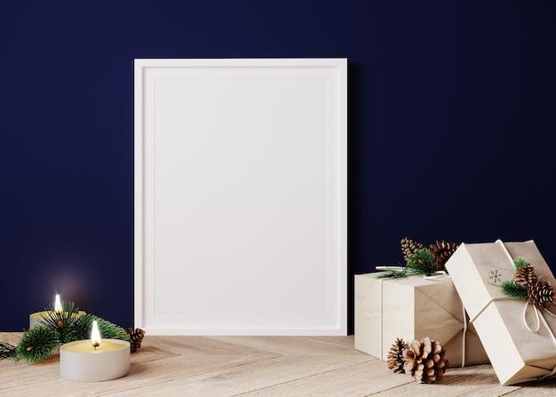 Вертикальный макет плаката с белой рамкой, украшенной елкой, свечами и подарочной коробкой на синем фоне стены