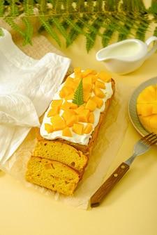 黄色の背景にマンゴーとホイップクリーム、家庭料理、マンゴーデザートと垂直パウンドケーキ