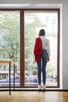 Vertical rearview shot of a stylish woman standing near the window looking out lifestyle recreation coziness home future youth planning concept.