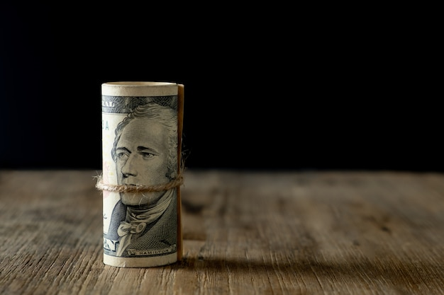 Vertical roll of american dollars banknotes on old wooden table