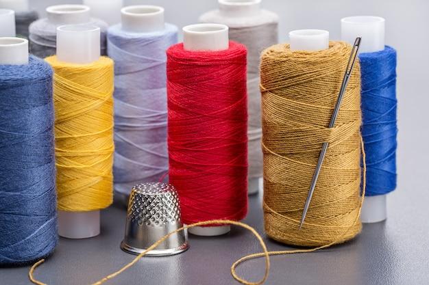 Вертикальный ряд витков с яркими нитками, большая игла и наперсток.