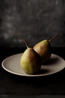 白い皿に梨の垂直の選択的なクローズアップショット