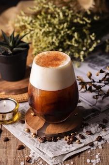 Primo piano verticale del fuoco selettivo di un bicchiere di caffè fresco