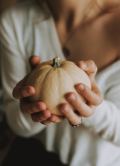 Vertical selective focus of a female holding a pumpkin
