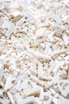 Vertical selective focus shot of all white toy brick building blocks