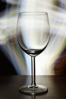 Vertical selective focus shot of an empty wine glass with blurry lights