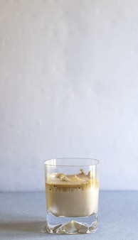 Vertical selective focus shot of a glass of coffee on a blue surface
