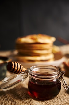 Vertical selective focus shot of a jar of honey with apple pancakes on the background