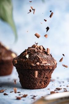 초콜릿 칩이 떨어지는 파란색 표면에 초콜릿 컵 케이크의 수직 선택적 초점 샷