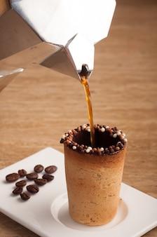비스킷으로 만든 컵에 쏟아지는 커피의 수직 선택적 초점 샷