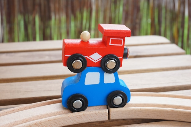 Vertical selective focus shot of a red wagon and a blue car placed on each other on a wooden table