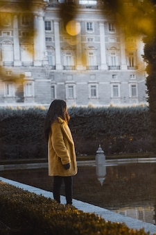 Vertical selective shot of a female wearing yellow coat standing by the water near a white building