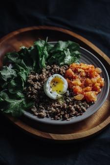 Colpo selettivo verticale di un uovo, di un grano saraceno e delle verdure affettati su un piatto