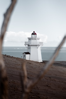 Vertical selective shot of a white lighthouse on a sandy seashore