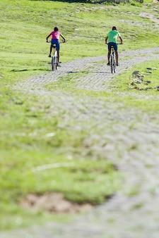 Вертикальный неглубокий фокус двух африканских мальчиков, езда на велосипедах