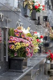 Вертикальный снимок букетов в мелком фокусе под темными мраморными надгробиями на кладбище
