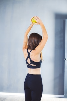 Vertical shallow focus shot of a woman in sportswear exercising with a ball