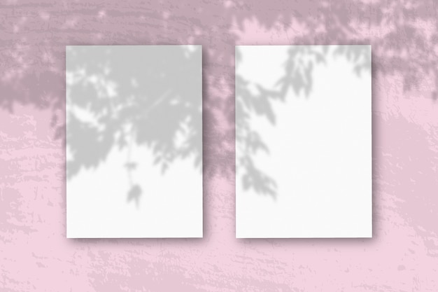 Vertical sheets of textured white paper on soft pink table background mockup with an overlay of plant shadows