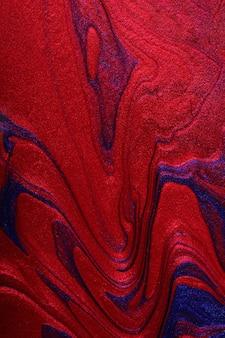 Вертикальный мерцание красный и синий абстрактный фон. концепция макияжа. красивые пятна жидких лаков для ногтей. флюид-арт, техника заливки. скопируйте место для размещения текста или логотипа.