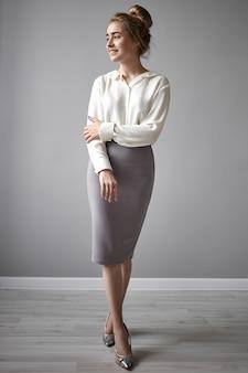 フォーマルな白いブラウス、チューブグレーのスカート、ハイヒールの靴を身に着けて、閉じた姿勢で立って、かわいい笑顔で目をそらして孤立したポーズをとる美しい陽気な若い女性の垂直ショート