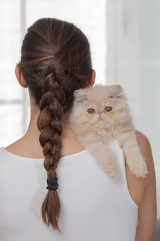 Vertical shot of an adorable domestic cat on a females' shoulder