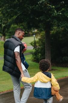 Colpo verticale di un bambino afro-americano e suo padre nel parco
