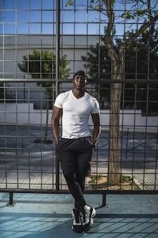 Vertical shot of an african-american male in a white shirt leaning on a fence