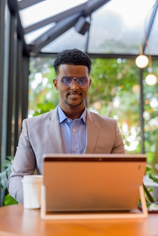 Vertical shot of african businessman at coffee shop using laptop computer