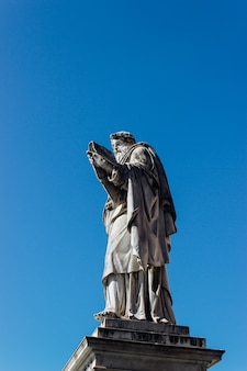 Vertical shot of an ancient historic statue touching the clear blue sky
