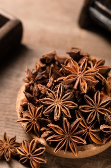 Vertical shot of anise stars on a wooden table