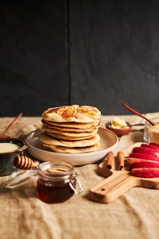 Vertical shot of apple pancakes on a plate with apple slices honey and ingredients on the side