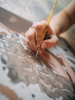 Vertical shot of an artist painting on the canvas