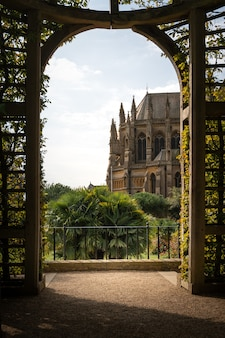 Vertical shot of the arundel castle and cathedral from a beautiful arch covered in green foliage