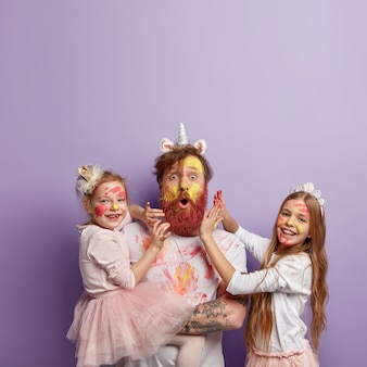 Vertical shot of astonished red haired man wears unicorn horn, plays with two small girls, have fun with colors, paint faces and clothes, being in good mood, isolated over purple wall. family concept