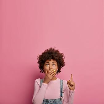 Inquadratura verticale di una donna sbalordita che copre la bocca, rimane senza parole, mostra qualcosa di inquietante, punta il dito anteriore verso l'alto, mostra il pericolo, vestita in modo casual, posa contro il muro rosa pastello