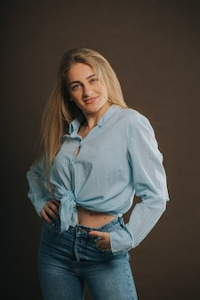 Vertical shot of an attractive blonde female in jeans and a short shirt posing on a brown wall