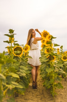Vertical shot of an attractive blonde female in a white dress posing in a sunflower field