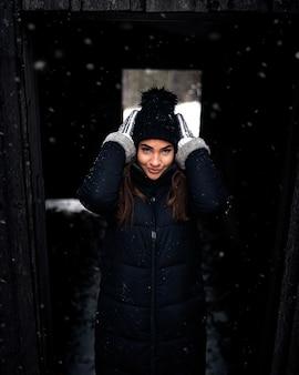 Colpo verticale di una femmina attraente che fissa il suo berretto a maglia