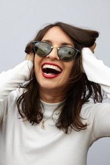 Colpo verticale di una donna attraente che ride di gioia